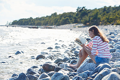 Woman reading book on beach - p312m1210897 by Johan Alp