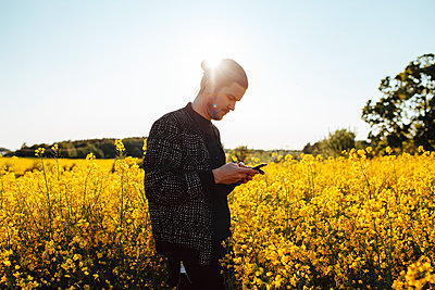 A young man outdoors looking at his cell phone - p352m1523652 by Benjamin Rudström