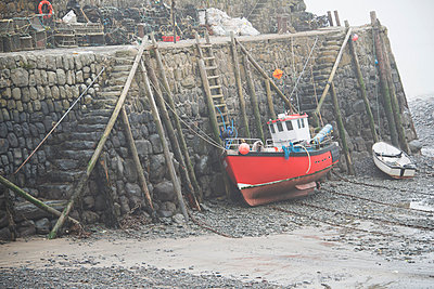 Ancient pier at Clovelly at low tide with fishing boats in foreground; Clovelly, Devon, England - p442m1033817 by Derelie Cherry