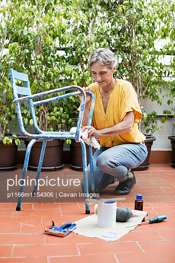 Full length of mature woman painting chair at yard - p1166m1154306 by Cavan Images