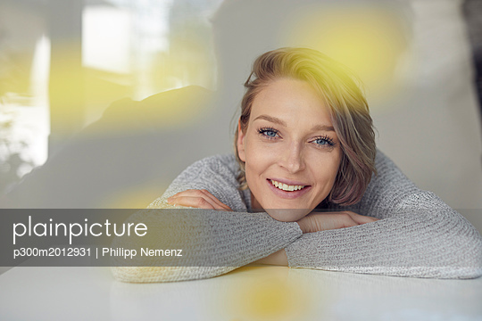 Portrait of smiling blond woman leaning on table - p300m2012931 von Philipp Nemenz