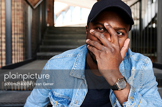Portrait of man covering face with his hand - p300m2140074 by Ivan Gener