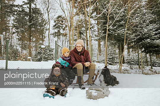 Mother with daughters and Border Collie sitting on snow covered field against trees - p300m2251115 by Frederik Franz