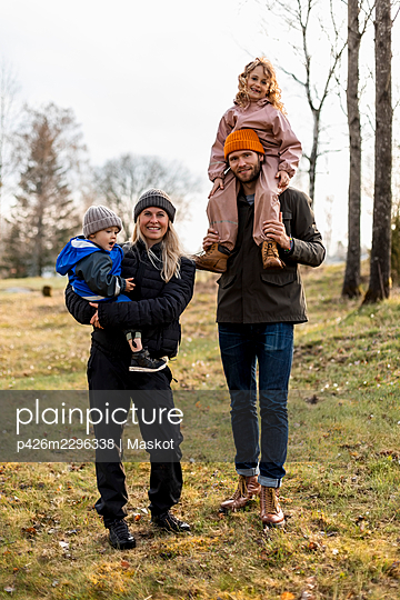 Full length portrait of family standing together at park - p426m2296338 by Maskot