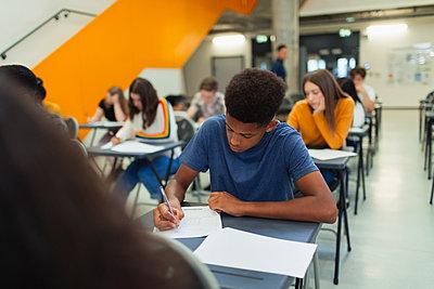 Focused high school boy student taking exam at desk - p1023m2190071 by Paul Bradbury