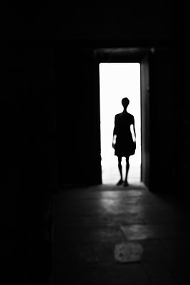 Silhouette of a woman standing in the door of a church - p1580m2214955 by Andrea Christofi