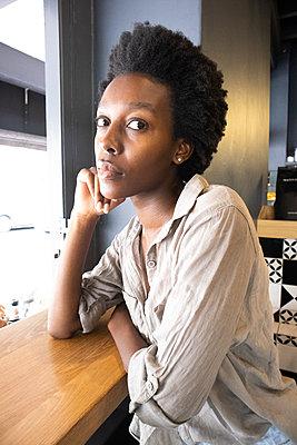 Junge afrikanische Frau in einem Bistro - p1640m2260113 von Holly & John