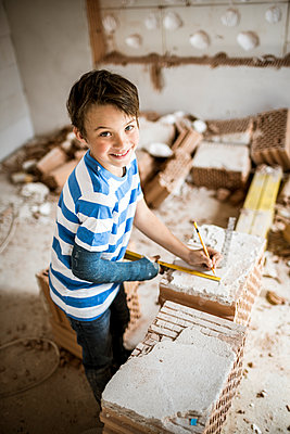 Smiling boy measuring brick while standing at house during renovation - p300m2287714 by Epiximages