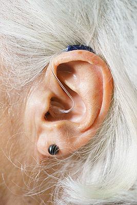 Close-up of senior woman's ear wearing hearing aid - p301m1498514 by Halfdark