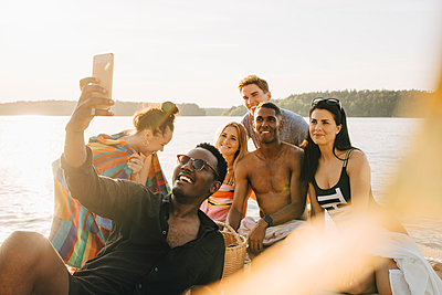 Man taking selfie with happy friends through smart phone on jetty in summer - p426m2097533 by Maskot