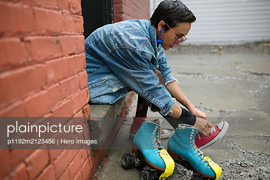 Cool young woman putting on roller skates in alley - p1192m2123456 by Hero Images