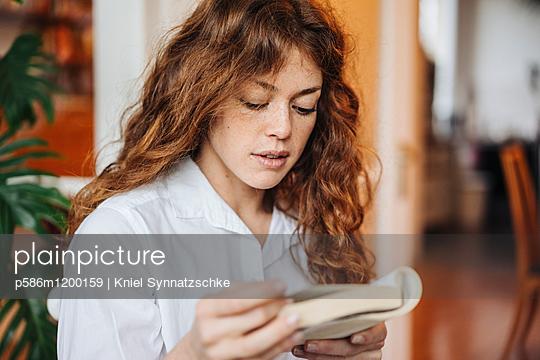 Junge Frau liest ein Buch - p586m1200159 von Kniel Synnatzschke
