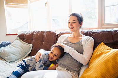 Affectionate mother and toddler son cuddling on living room sofa - p1023m2016666 by Sam Edwards