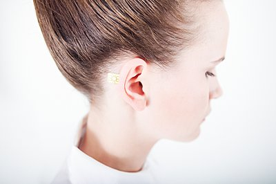 Woman with computer chip implant on ear - p1093m2223245 by Sven Hagolani