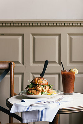 Side view of chicken burger and bloody mary at brunch table - p1166m2191879 by Cavan Images
