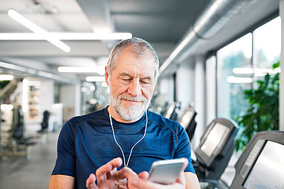Senior man with smartphone and earphones in gym - p300m1449329 by HalfPoint