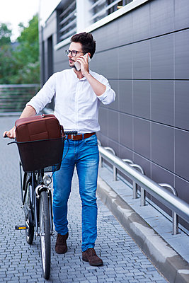 Businessman on the phone pushing his bicycle - p300m2012217 by gpointstudio