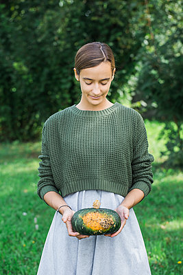 Young woman with pumpkin in the garden - p300m2041621 by Alberto Bogo