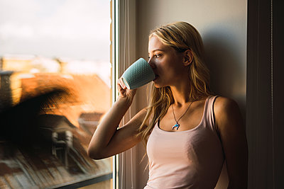 Blond young woman drinking coffee from mug looking out of window - p300m2042330 by Kike Arnaiz