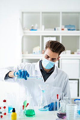 Male scientist filling flask with medicine through funnel in laboratory during COVID-19 - p300m2265376 by Giorgio Fochesato