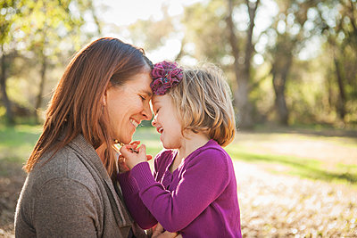 Mother and daughter hugging in park - p555m1409571 by Shestock