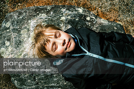 Child lying down on rock and enjoying the first warm sun rays on face - p1166m2269245 by Cavan Images