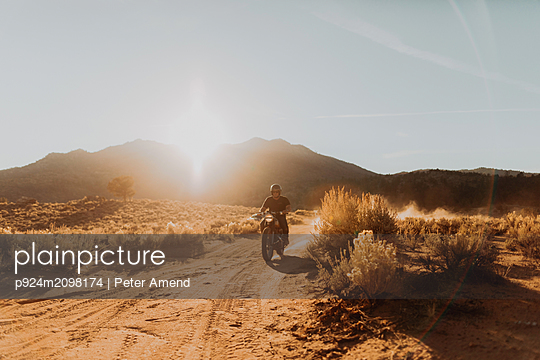 Motorbiker riding through landscape of Kennedy Meadows, California, US - p924m2098174 by Peter Amend