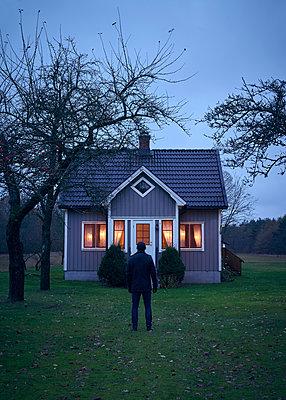 Mann steht vor schwedischem Haus - p1124m1193526 von Willing-Holtz