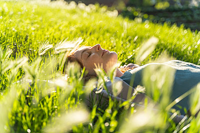 Young redheaded woman lying on meadow in a park - p300m2113830 by VITTA GALLERY