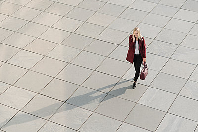 View from above of blond businesswoman using smartphone, walking on concrete ground - p300m2155139 by Hernandez and Sorokina