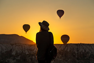 Rear view of silhouette young woman looking at hot air balloons while standing on land at Goreme, Cappadocia, Turkey - p300m2198487 by Konstantin Trubavin