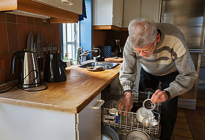 Man putting dishes into dishwasher - p312m2139308 by Pernille Tofte