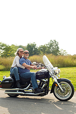 Older couple riding motorcycle - p555m1411195 by Alberto Guglielmi