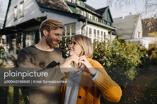 Smiling couple standing in front of their home shaping a heart with their hands - p300m2166640 von Kniel Synnatzschke