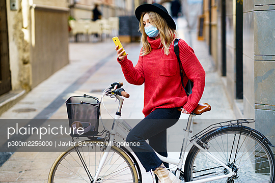 Young woman wearing face mask mask using mobile phone while sitting with bicycle on footpath - p300m2256000 by Javier Sánchez Mingorance