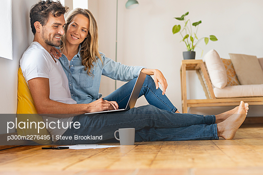 Mid adult man using laptop while sitting with girlfriend at home office - p300m2276495 by Steve Brookland