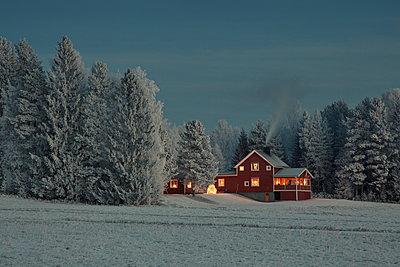 Erleuchtetes Holzhaus an einem Winterabend - p235m1215183 von KuS