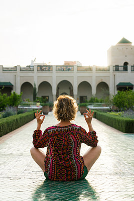 Morocco, Marrakesh, tourist sitting on the floor in a courtyard doing yoga - p300m1449797 by Kike Arnaiz
