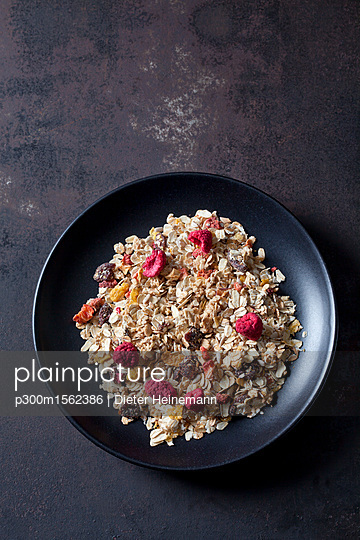 Bowl of fruit granola with dried raspberries, strawberries and cranberries - p300m1562386 by Dieter Heinemann