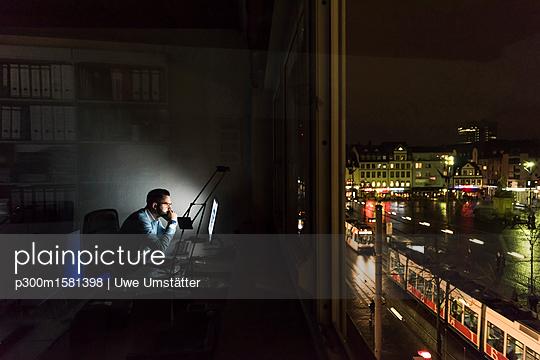 Businessman working on computer in office at night - p300m1581398 von Uwe Umstätter