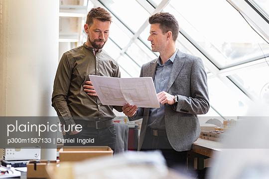 Two businessmen discussing plan in factory - p300m1587133 von Daniel Ingold