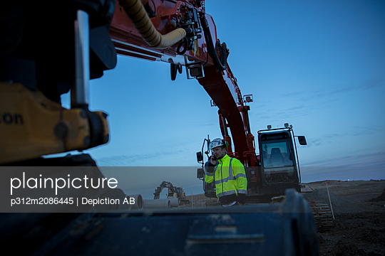 Worker in front of digger - p312m2086445 by Depiction AB