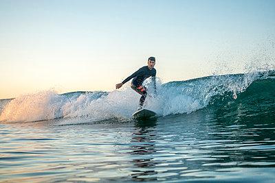 Man surfing on huge waves in sea against clear sky - p1166m1414549 by Cavan Images