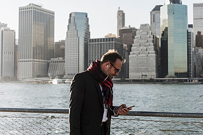 USA, Brooklyn, businessman with smartphone and earphones in front of Manhattan skyline - p300m1205082 by Uwe Umstätter