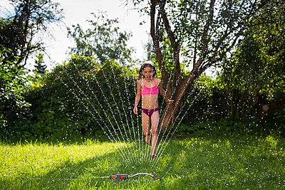 Little girl having fun with lawn sprinkler in the garden - p300m2004398 by Larissa Veronesi