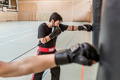 Coach and boxer practising at punchbags in sports hall - p300m2144829 von Stefanie Baum