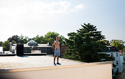 Man standing on roof - p341m2013749 by Mikesch
