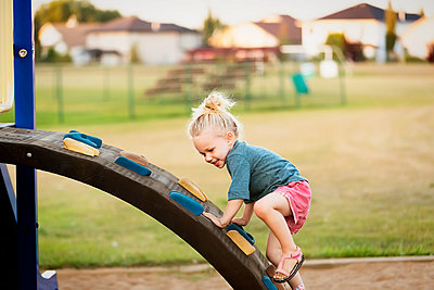 A young girl with blond hair playing in a playground and climbing up a rock ladder on a warm fall day; Spruce Grove, Alberta, Canada - p442m2004258 by LJM Photo