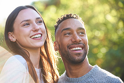 Close-up of smiling young couple looking away in public park - p623m2294779 by Eric Audras
