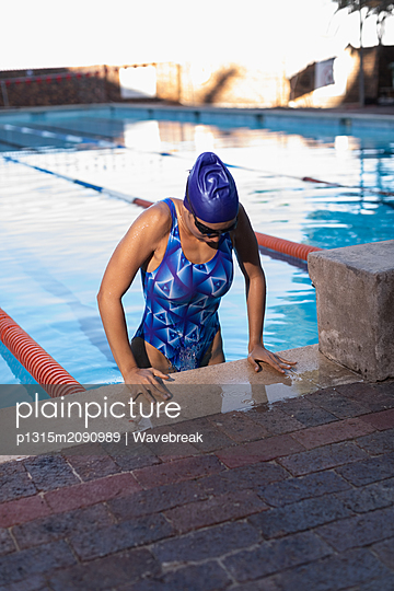 Female swimmer coming out of swimming pool - p1315m2090989 by Wavebreak